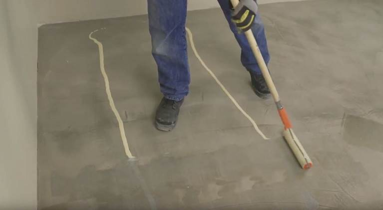 Flooring installer applying RollFast,  an installer-friendly, roller applied adhesive for LVT and LVP floor installations.